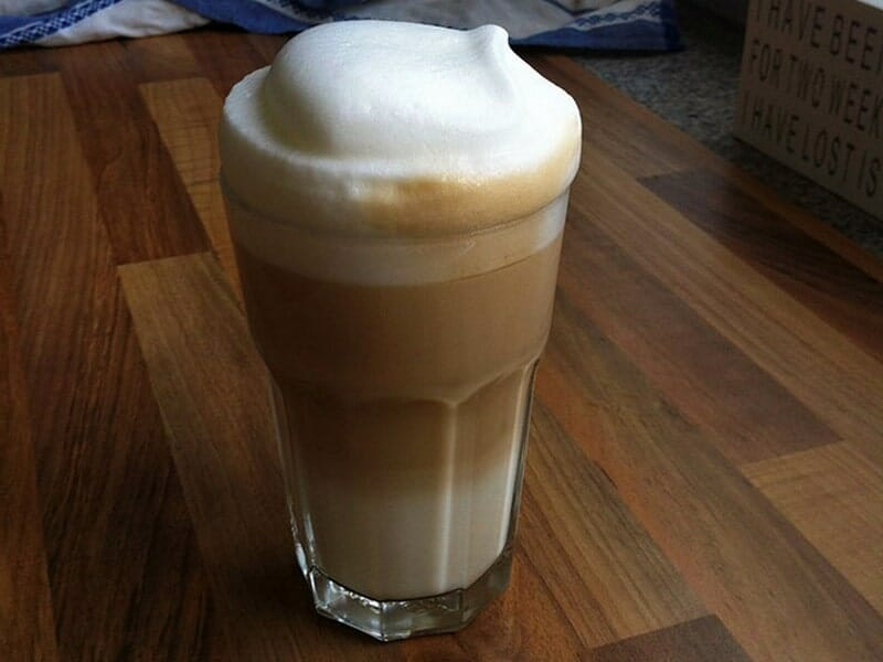 Latte Macchiato Served in a tall glass on a wooden table