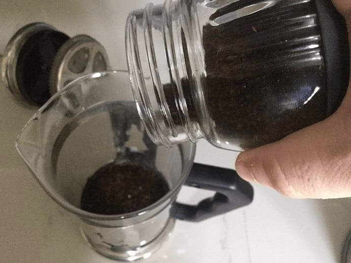 Adding ground coffee to French Press