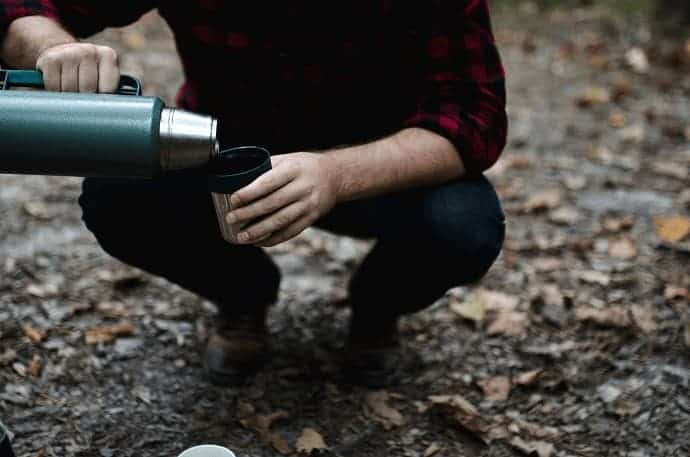 man kneeling with a Thermal flask