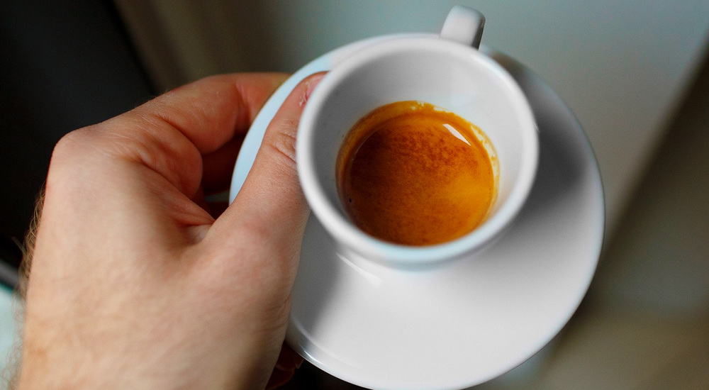 hold a white espresso demitasse cup