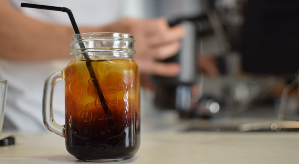 Mason jar with cold brew coffee and a black straw