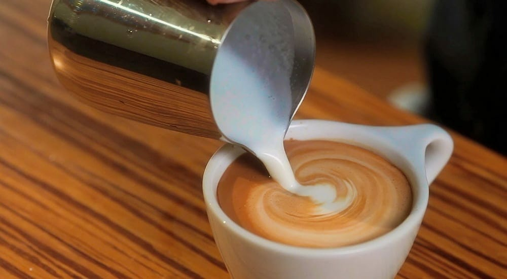 a photo of thick froth being poured out from one of the best milk frothers